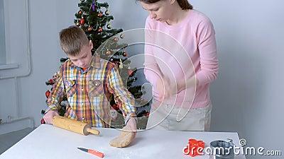 Mam en zoon maken ontbijtdeeg voor kerstkoekjes thuis stock video