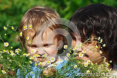Mama joven con su hijo entre las margaritas del verano