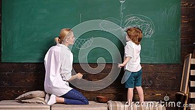 Mama und ihr Sohn zeichnen in der Schule mit Kreide auf grüner Tafel, Rückansicht Frauen und Jungen zeichnen Zurück zur Schule stock video footage