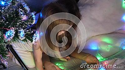 Mama und Tochter am Weihnachtsabend spielen und schauen sich in einem Kinderzimmer in einem Zelt mit Garnelen Karikaturen auf Tab stock video