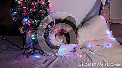 Mama und Tochter am Weihnachtsabend spielen und schauen sich in einem Kinderzimmer in einem Zelt mit Garnelen Karikaturen auf Tab stock video footage