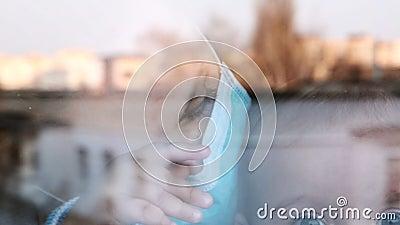 Maman avec un petit enfant dans un masque médical regarde par la fenêtre pendant la quarantaine en raison de coronavirus, virus d banque de vidéos
