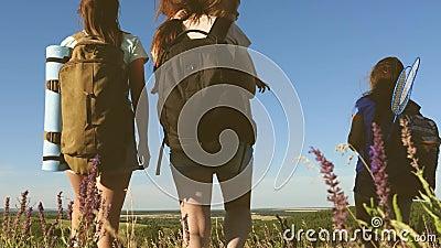 Maman et enfants traversent le champ avec des sacs à dos en fleurs en été Vie familiale Les touristes et un petit banque de vidéos