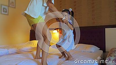 Maman et fille sautent sur le lit dans la chambre d'hôtel banque de vidéos