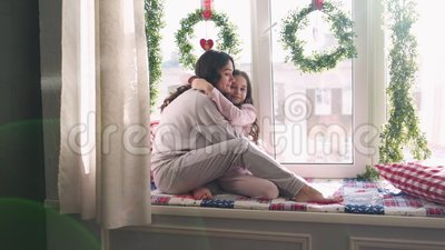 Mamma e figlia sono sedute alla finestra sullo sfondo delle decorazioni natalizie famiglia felice mamma e bambino video d archivio