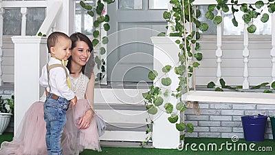 Mamma en zoonsrit op de tuinschommeling stock video
