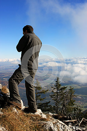 Man admiring the view from the top of the mountain