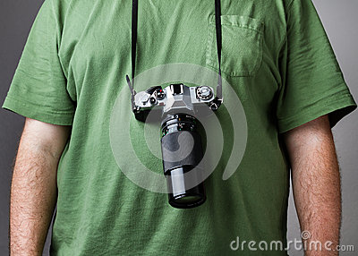 Man against gray background with camera strapped to him
