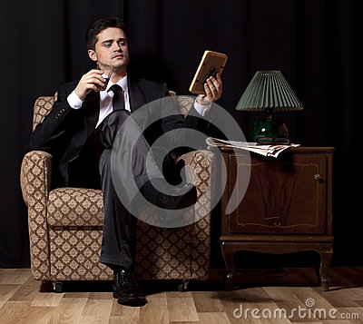 Man with alcohol sitting in vintage armchair