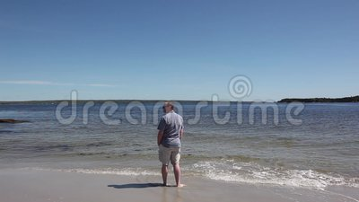 Man alone on beach. A man stands alone on the shoreline looking out to the ocean stock footage