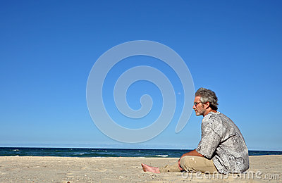 A man alone on white sandy beach