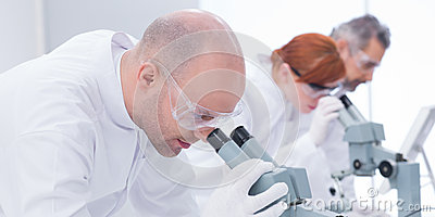 Man analyzing under microscope
