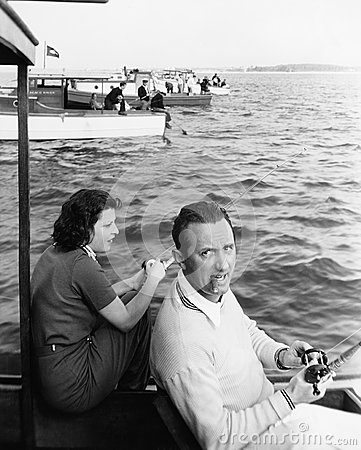 Free Man And Woman Sitting On A Boat On A Lake With Their Fishing Rod Stock Photography - 52015002