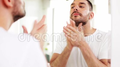 Man applying after shave oil to face at bathroom. Beauty, skin care and people concept - smiling young man applying after shave oil to face and looking to mirror stock video footage