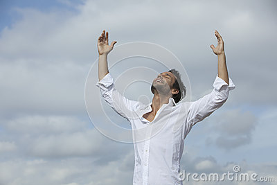 Man with arms raised under cloudy sky