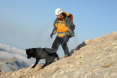Man is ascending the mountain with his dog