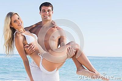 Man att bära hans nätta flickvän som ler på kameran