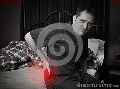 Man with Back Pain Sitting on Bed