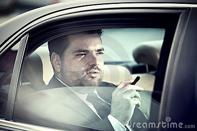 Man in the back seat of a car smoking
