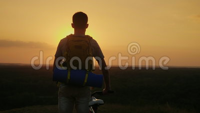 A man with a backpack and a bicycle. It stands and looks at the horizon where the sun sets. Cycling and adventure. 4K video stock video