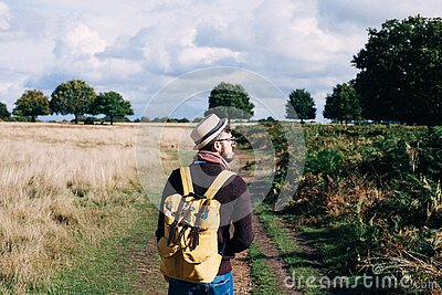 Man With Backpack Walking On Pathway Between Field At Daytime Free Public Domain Cc0 Image