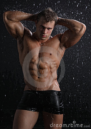 Man barn för regn för muskeln posera sexigt under vått