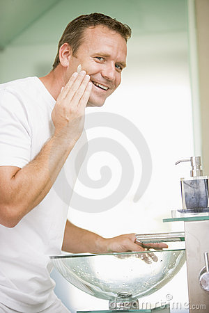 Man in bathroom applying shaving cream