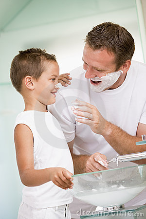 Man in bathroom putting shaving cream on young boy