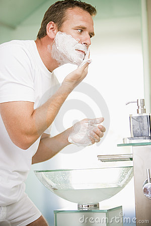 Man in bathroom shaving