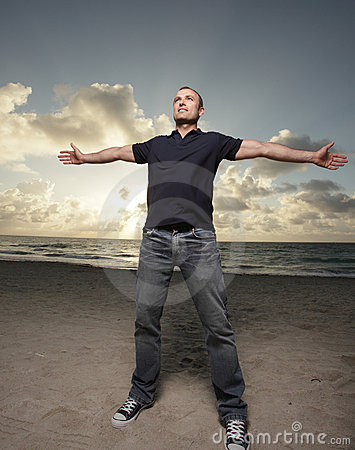 Man on the beach with arms extended