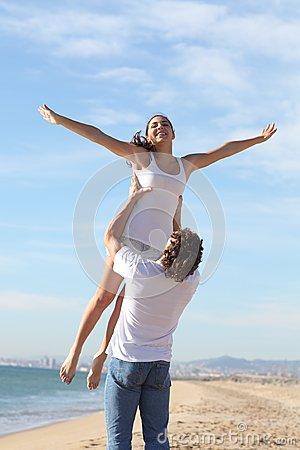 Man on the beach raising his girlfriend