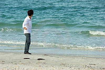 Man on beach throwing rocks into ocean