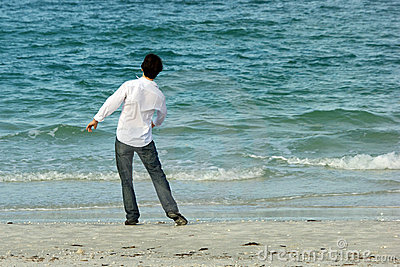 Man on beach throwing rocks into sea