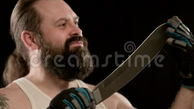 Man with beard, gloves in black studio, runs his fingers along blade of machete. A stern adult man with a beard, a tattoo, gloves in a black studio, runs his stock footage