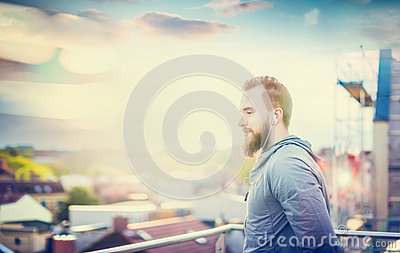 Man with a beard and short hair, in a gray jacket, standing on the background of the urban landscape with clouds setting sun Stock Photo
