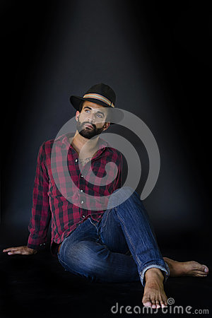 Man with beard, sitting in red shirt and wearing a hat