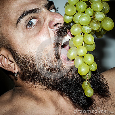Man with beard who eats voraciously grapes