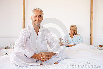Man on bed with his wife in the background