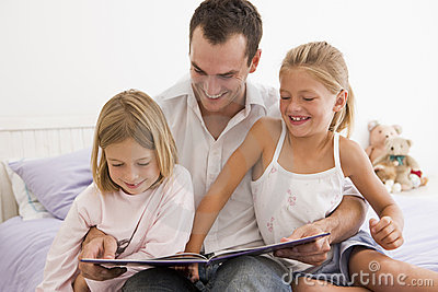 Man in bedroom with two young girls reading book