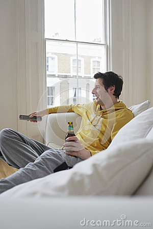 Man With Beer Bottle Watching TV On Sofa