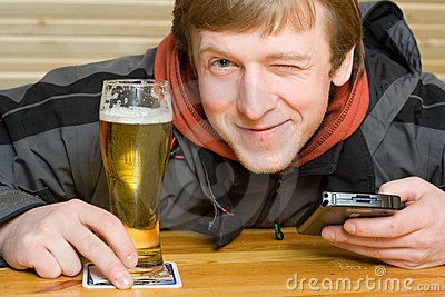 Man with beer and palm-size computer