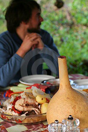 Man behind table with fish soup and wine