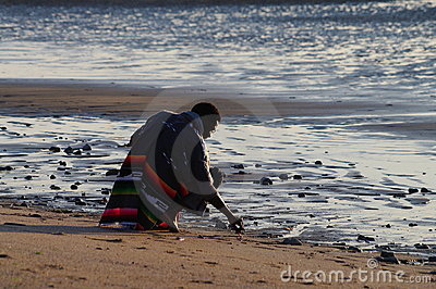 A man on bended knees at the beach