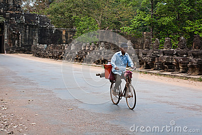 Man bikes past ruins at Angkor Wat Editorial Stock Photo