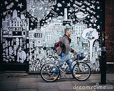 Man In Black Jacket Holding A Black Hardtail Bike Near Black And White Art Wall Free Public Domain Cc0 Image