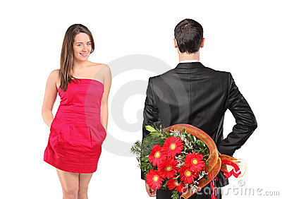 Man in black suit hiding flowers and woman