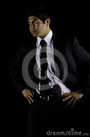 Man in black suit and tie with a gun in waist band