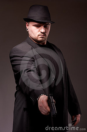 Man in black suite with gun.