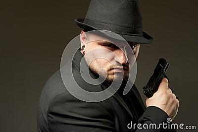 Man in black suite with gun.