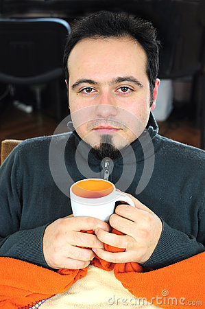 Man in blanket holding cup of tea
